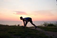 Giovane allungamento maschio prima del corso di formazione di forma fisica al parco Giovane in buona salute che si scalda all'ape Fotografie Stock