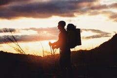 Giovane alpinista che sta con lo zaino sopra una montagna Fotografie Stock