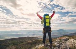 Giovane alpinista che sta con lo zaino sopra una montagna Immagine Stock Libera da Diritti
