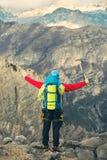 Giovane alpinista che sta con lo zaino sopra una montagna Fotografia Stock