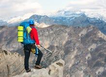 Giovane alpinista che sta con lo zaino sopra una montagna Immagine Stock
