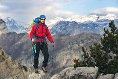 Giovane alpinista che sta con lo zaino sopra una montagna Fotografie Stock Libere da Diritti
