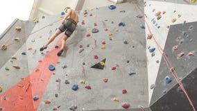 Giovane ambizioso libero che scala sulla parete artificiale stock footage