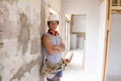 Giovane apprendista attraente e sicuro di lavoro del costruttore e del costruttore che impara e che lavora al collare blu del sit Immagine Stock Libera da Diritti