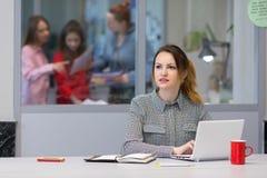 Giovane apprendista femminile che lavora al computer portatile nell'interno dell'ufficio Immagine Stock Libera da Diritti