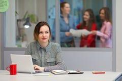 Giovane apprendista femminile che lavora al computer portatile nell'interno dell'ufficio Fotografie Stock Libere da Diritti
