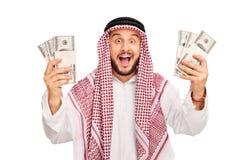 Giovane arabo emozionante che tiene poche pile di soldi Fotografia Stock Libera da Diritti