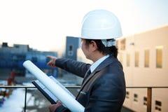 Giovane architetto che indica alla costruzione di edifici Immagine Stock