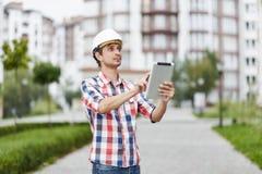Giovane architetto davanti alla costruzione di appartamento Fotografia Stock Libera da Diritti