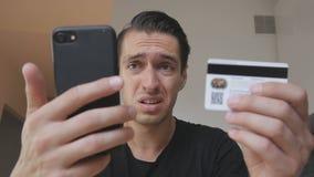 Giovane arrabbiato che compra gli usi online un telefono e una carta di credito e che ritiene che sia ingannato Internet infruttu stock footage