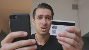 Giovane arrabbiato che compra gli usi online un telefono e una carta di credito e che ritiene che sia ingannato Internet infruttu video d archivio