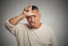 Giovane arrabbiato che mostra il segno del perdente sulla fronte Fotografie Stock Libere da Diritti