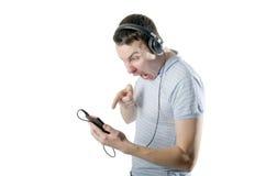 Giovane arrabbiato con le cuffie che guardano al telefono Fotografia Stock Libera da Diritti