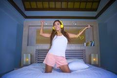 Giovane ascoltare misto di bella e dello studente etnia latina asiatica felice della donna la musica con le cuffie a letto che ca fotografie stock