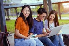 Giovane asiatico degli studenti che legge insieme studio del libro immagine stock