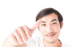 Giovane asiatico del primo piano che mostra i pollici su con il fondo bianco, Immagini Stock