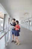 Giovane asiatico e donna che guardano al GUI di viaggio della destinazione Immagine Stock Libera da Diritti