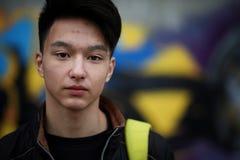 Giovane asiatico sulla via che posa alla macchina fotografica Fotografie Stock Libere da Diritti
