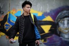 Giovane asiatico sulla via che posa alla macchina fotografica Immagine Stock