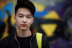 Giovane asiatico sulla via che posa alla macchina fotografica Fotografia Stock