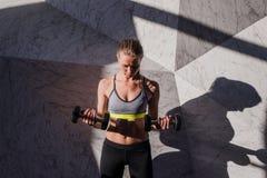 Giovane atleta attraente con l'ente muscolare che esercita crossfit Donna in abiti sportivi che fanno allenamento del crossfit co Immagine Stock