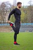 Giovane atleta attraente dell'uomo che si scalda allo stadio Immagini Stock