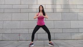 Giovane atleta castana felice della donna di forma fisica che fa allenamento all'aperto nella città sul fondo urbano stock footage