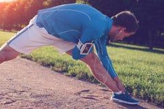 Giovane atleta che fa allungamento di riscaldamento prima dell'allenamento all'aperto Immagini Stock