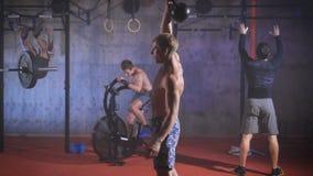 Giovane atleta che fa gli esercizi con kettlebell in mani differenti stock footage