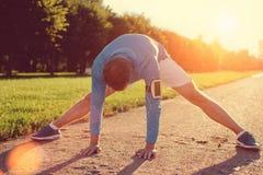 Giovane atleta che fa riscaldamento prima dell'allenamento nel parco Immagine Stock