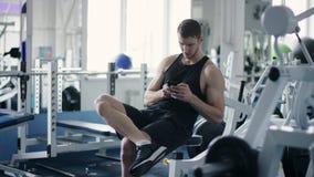 Giovane atleta che manda un sms sullo smartphone mentre riposando durante l'allenamento in una palestra stock footage