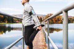 Giovane atleta con lo smartphone che allunga nel parco Immagini Stock Libere da Diritti