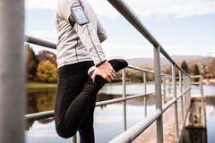 Giovane atleta con lo smartphone che allunga nel parco Fotografie Stock