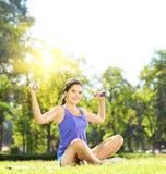 Giovane atleta femminile in abiti sportivi che si esercita con le teste di legno dentro Fotografia Stock