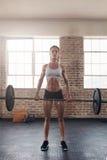 Giovane atleta femminile adatto che solleva i pesi pesanti Fotografie Stock Libere da Diritti