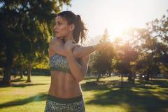 Giovane atleta femminile che allunga prima dell'addestramento di forma fisica Immagine Stock