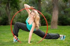 Giovane atleta femminile con il hula-hoop nel parco Fotografia Stock Libera da Diritti