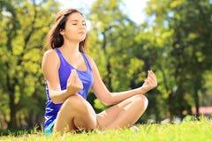 Giovane atleta femminile nel meditare degli abiti sportivi messo su erba Fotografie Stock