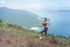 Giovane atleta femminile snello che fa cardio esercizio che va sulla montagna con il mare nel fondo immagine stock