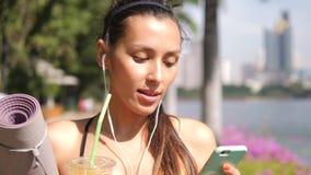 Giovane atleta Girl Using Smartphone della corsa mista e succo d'arancia fresco bevente dopo pratica di yoga di mattina nel parco video d archivio