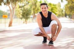 Giovane atleta latino che lega le sue scarpe immagini stock