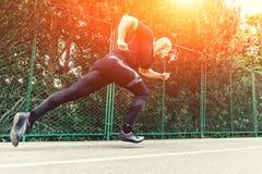 Giovane atleta maschio che lancia fuori dalla linea di inizio in una corsa Funzionamento del corridore sulla pista in stadio Immagini Stock