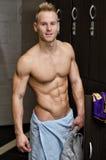 Giovane atleta maschio muscolare senza camicia nello spogliatoio della palestra Immagini Stock