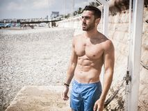 Giovane atletico che prende doccia sulla spiaggia fotografia stock