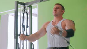 Giovane atletico che risolve sull'attrezzatura di esercizio di forma fisica alla palestra video d archivio