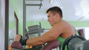 Giovane atletico che risolve sull'attrezzatura di esercizio di forma fisica alla palestra stock footage