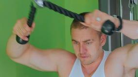 Giovane atletico che risolve sull'attrezzatura di esercizio di forma fisica alla palestra archivi video