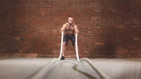 Giovane atletico con la corda di battaglia che fa esercizio nella palestra di formazione funzionale di forma fisica Movimento len video d archivio