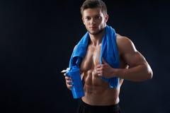 Giovane atletico senza camicia con un asciugamano e una bottiglia di acqua dopo Immagini Stock Libere da Diritti
