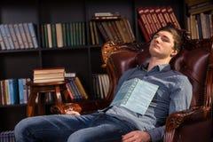 Giovane attraente addormentato in una biblioteca Immagini Stock Libere da Diritti